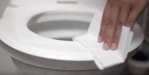 Hand wischt mit Toilettenpapier über einen weißen Toilettensitz - Reinigen des Toilettensitzes mit Desinfektionsliquid