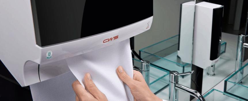 Ausschnitt Waschraum: Stoffhandtuchspender Paradise Dry Slim NT mit schwarzem Panel - Hände berühren ein Stück Handtuchrolle