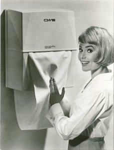 Handtuchspender -Hygienisches Händetrocknen: der erste Stoffhandtuchspender von CWS - historische Aufnahme - Dame beim Händetrocknen mit Stoffhandtuchrolle