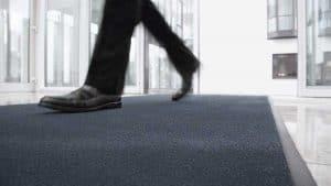 Mann läuft über Graue Scraper-Matte (Grobschmutzmatte)